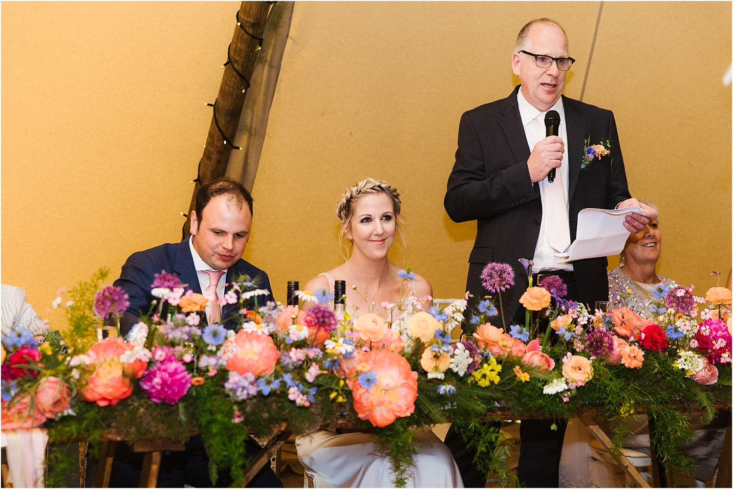 Bride enjoys her father's speech at Lancashire farm wedding. Reception flowers by Felicity Farm Flowers