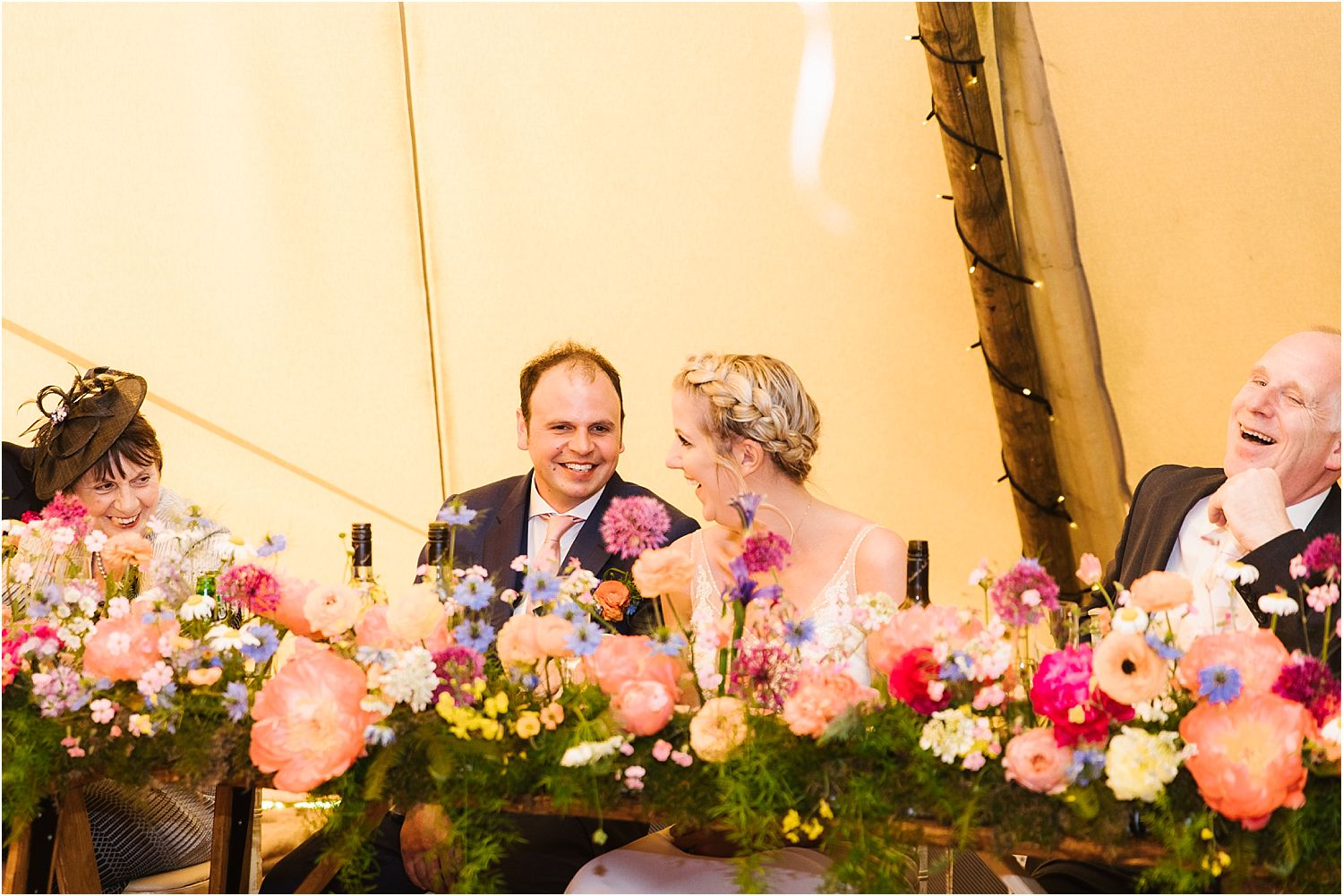 Bride, groom and top tabel guests laughing during Lancashire farm wedding reception