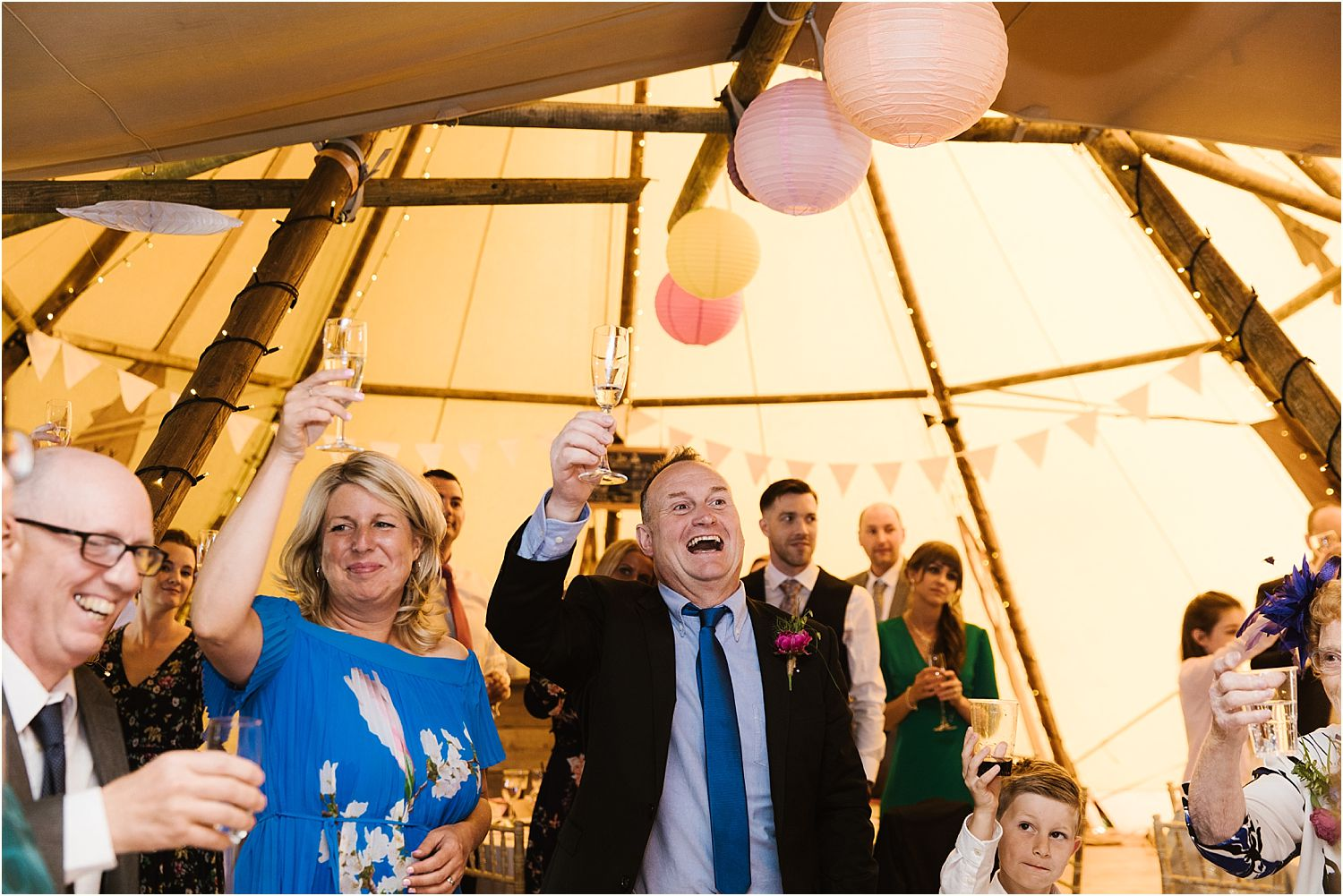Guests raise a glass to toast the bride and groom at Lancashire tipi wedding