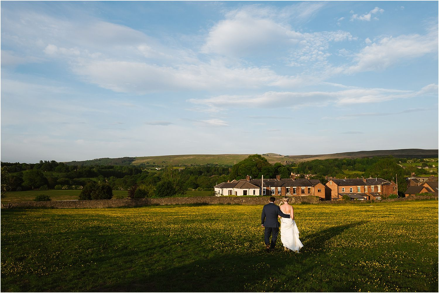Bride and groom walking towards venue across buttercup meadow in the evening of their Lancashire farm wedding
