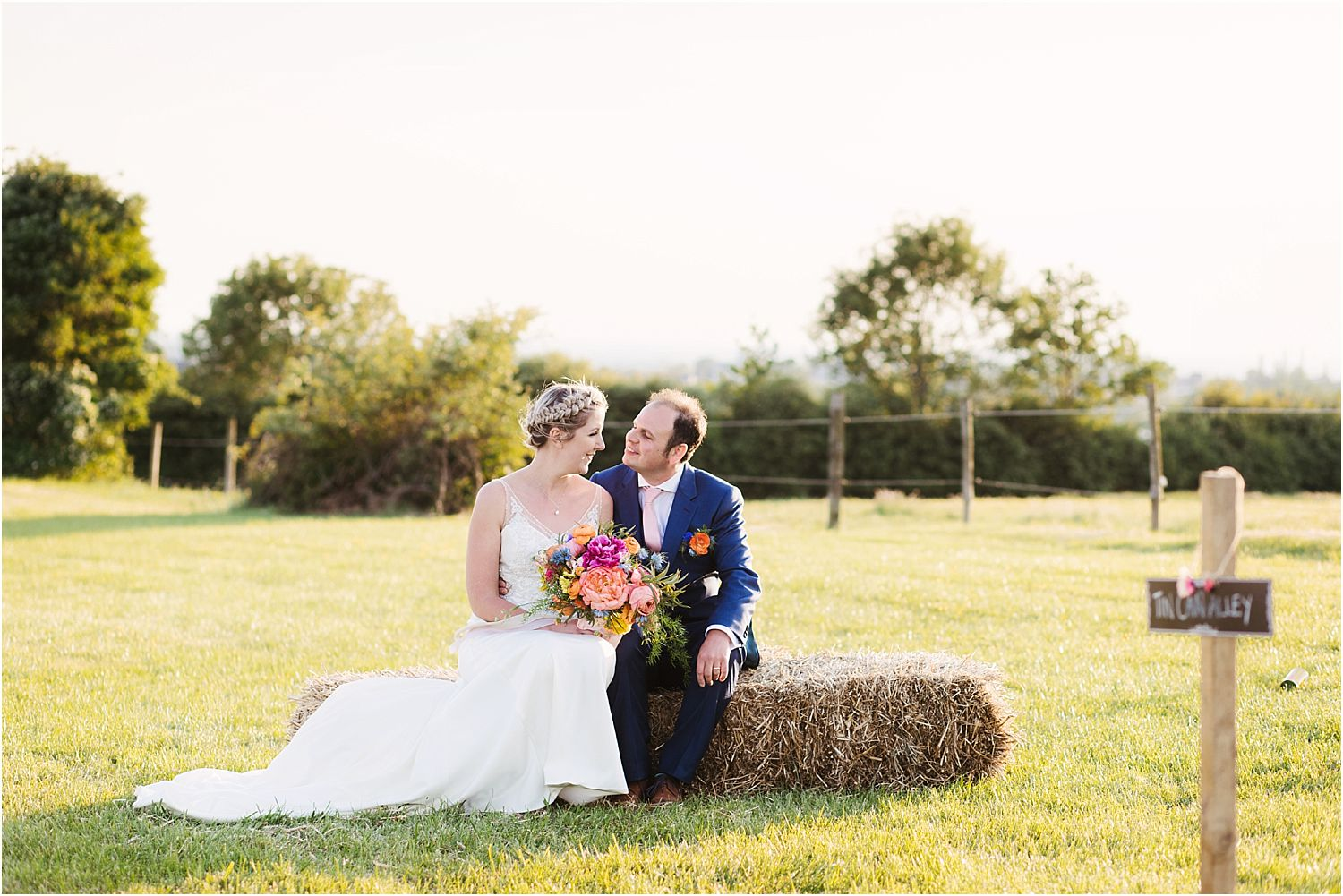 Bride and groom sitting on hay bale at Lancashire farm wedding
