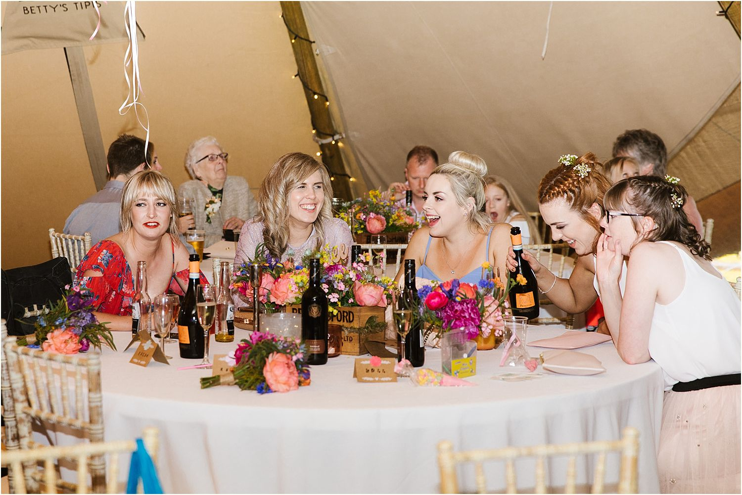 Guests enjoying evening reception in tipi by Betty's Tipis at Lancashire farm wedding