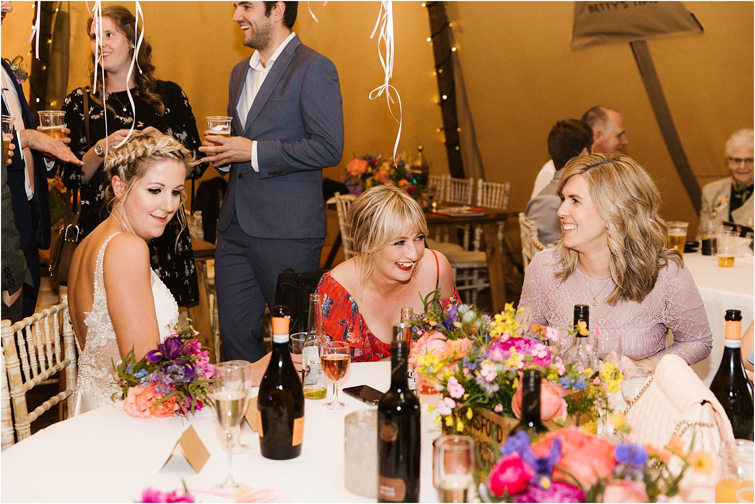 Bride and friends at evening reception of Lancashire farm wedding. Tipi by Betty's Tipis of Chorley