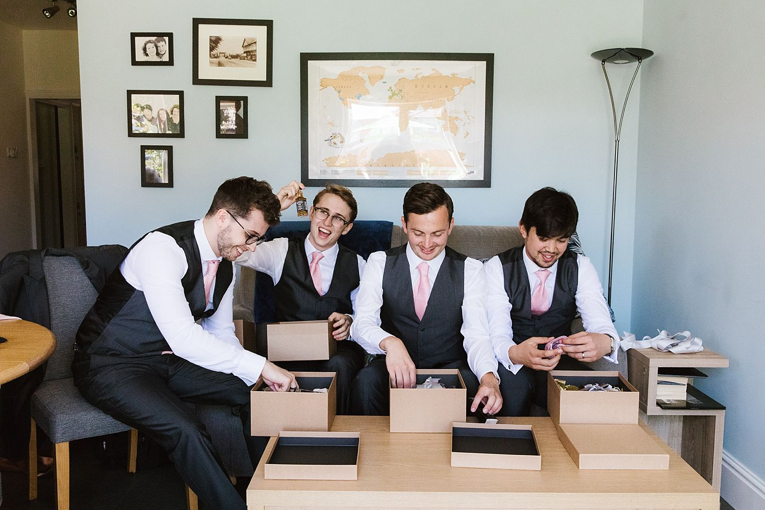 Best man and ushers open presents prior to the wedding at Sandhole Oak Barn, suits from The Grooms Room Essex