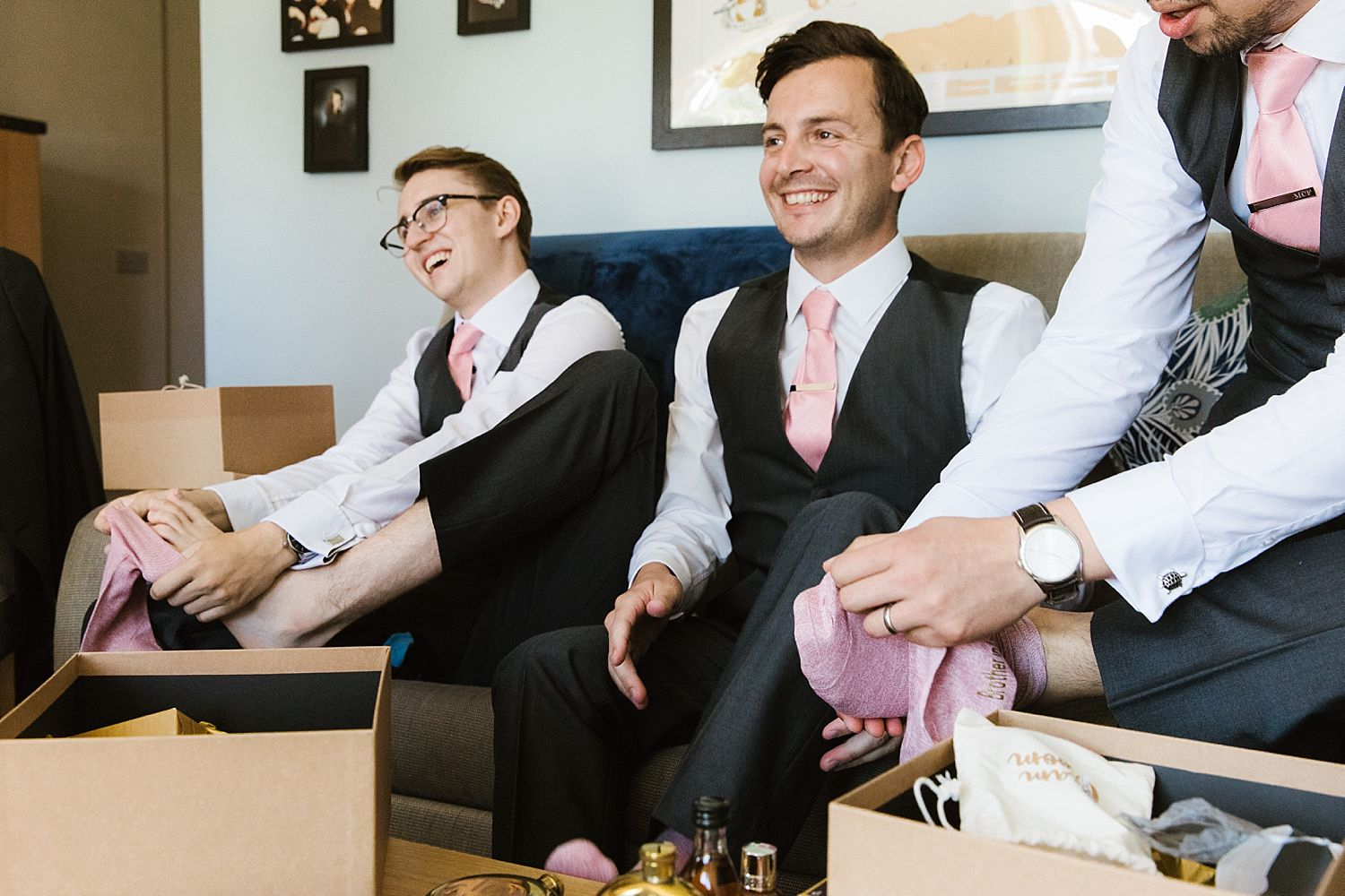 Groom and ushers putting their socks on at Sandhole Oak Barn wedding, suits from The Groom's Room, Essex.