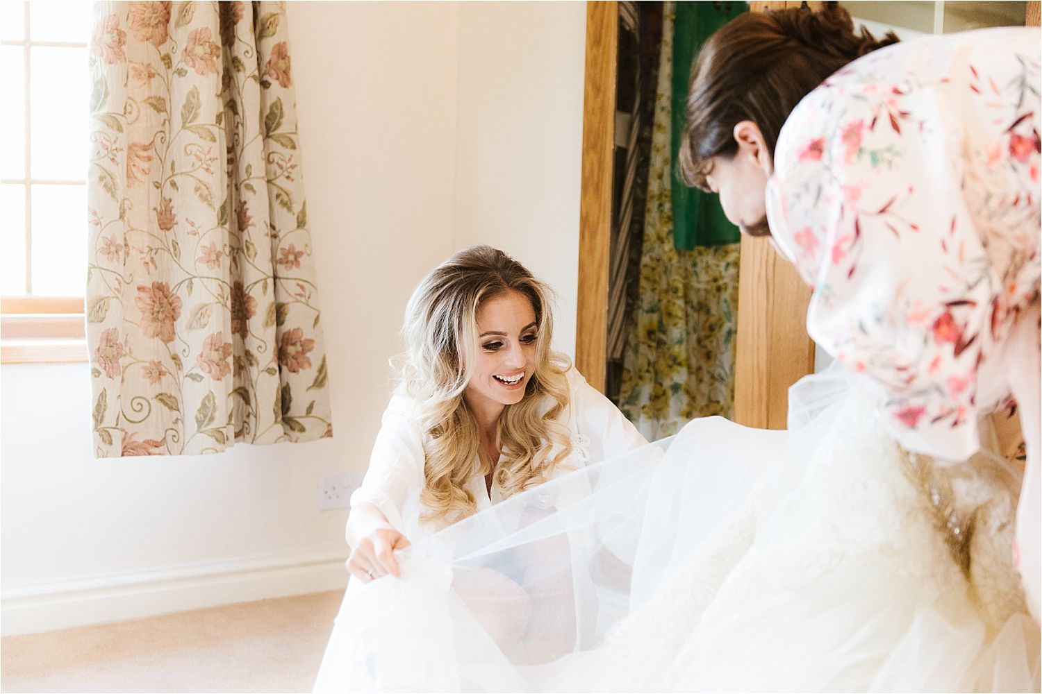 Bride and her mother organising net of wedding dress prior to Congleton wedding, Cheshire