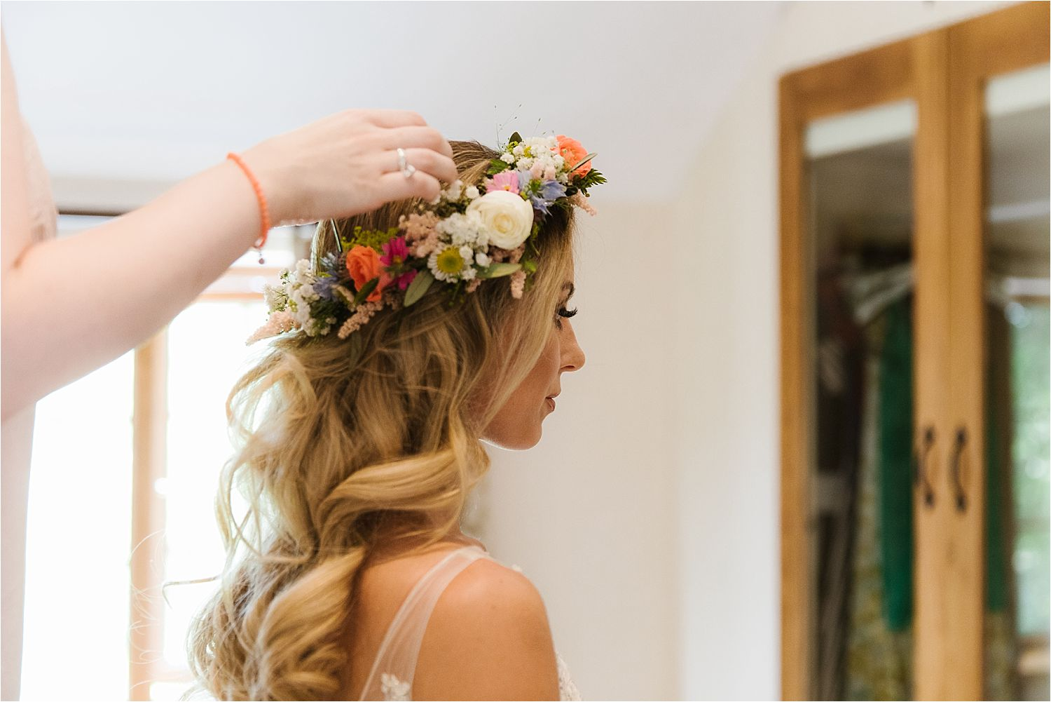 Floral Headress by Green Earth Flowers, being pinned in place by stylist Lizzie Griffiths