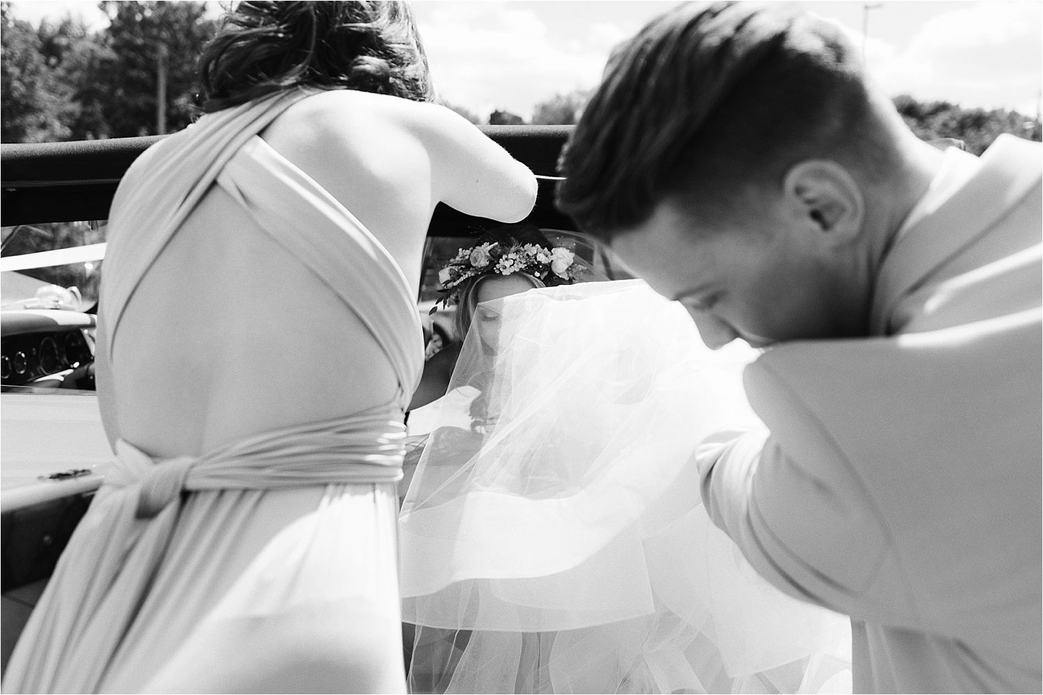Bridesmaid and usher help bride out of car, holding net of her dress.