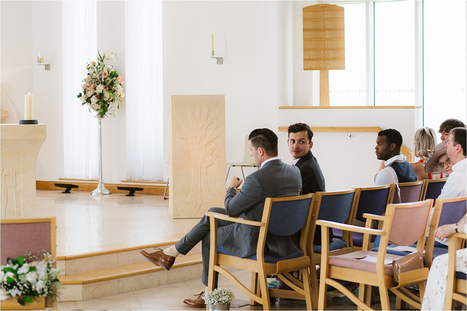 Bridegroom sits nervously whilst best man looks back at beginning of Cheshire wedding ceremony