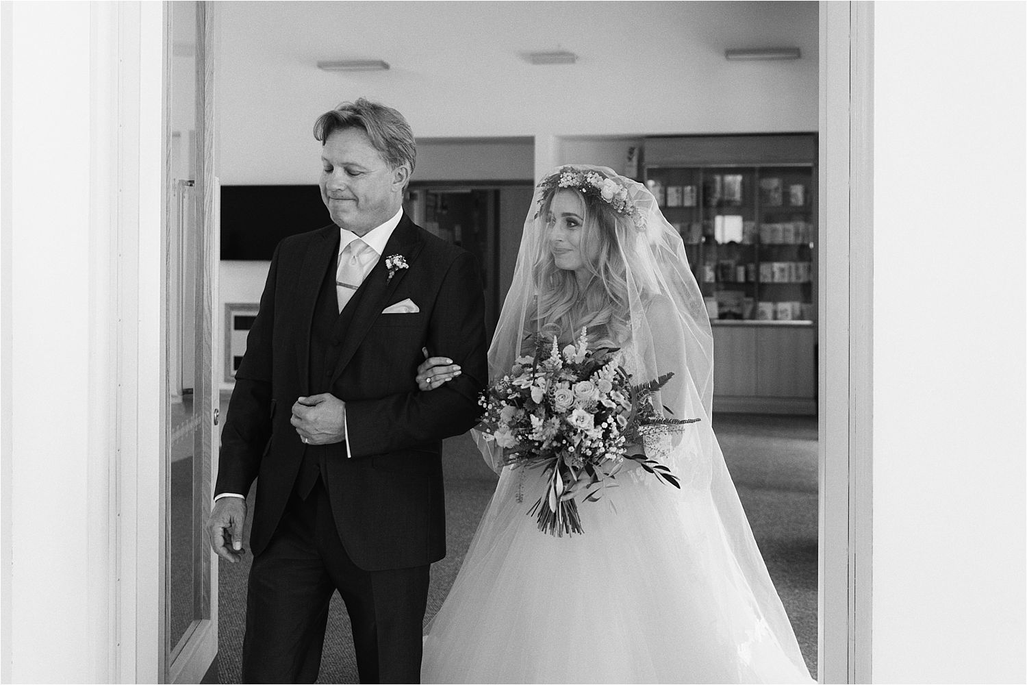 Bride and her father walkingin to church at Cheshire wedding. Bridal bouquet by Green Earth Flowers of Poynton