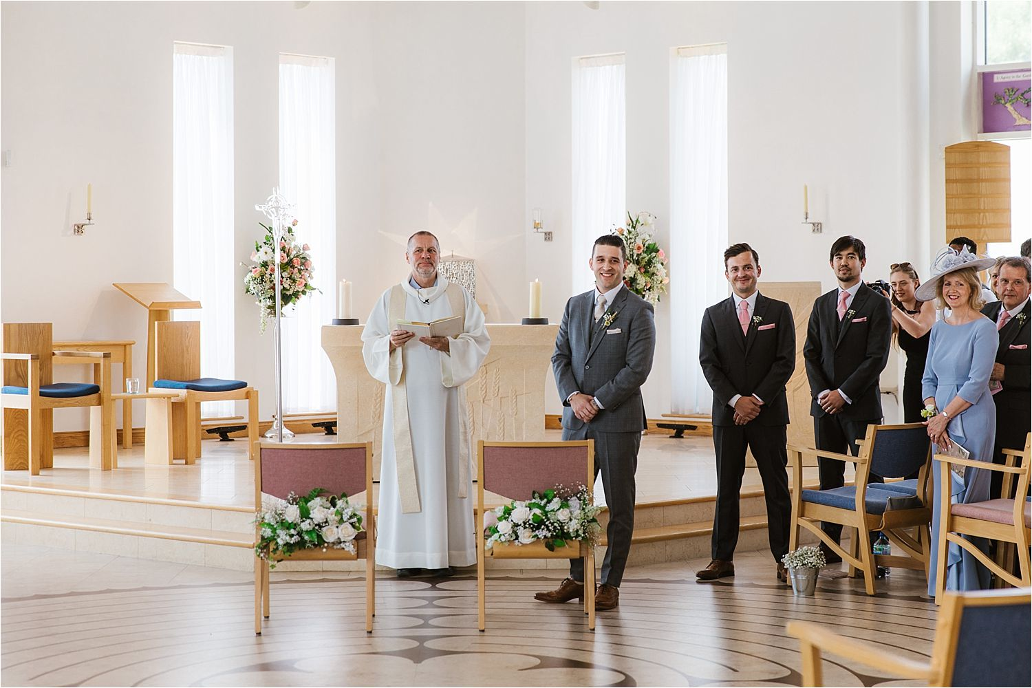 Bridegroom looks back to see his bride walking down the aisle at wedding ceremony in Cheshire