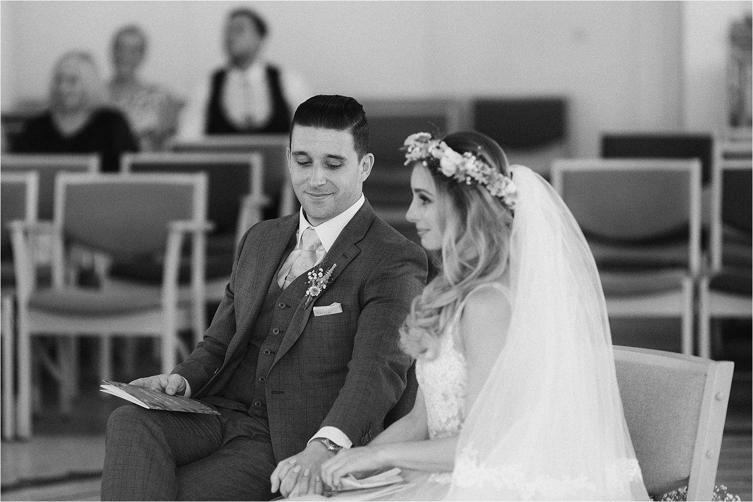 Bridegroom looks down at bride's hands during Cheshire wedding ceremony