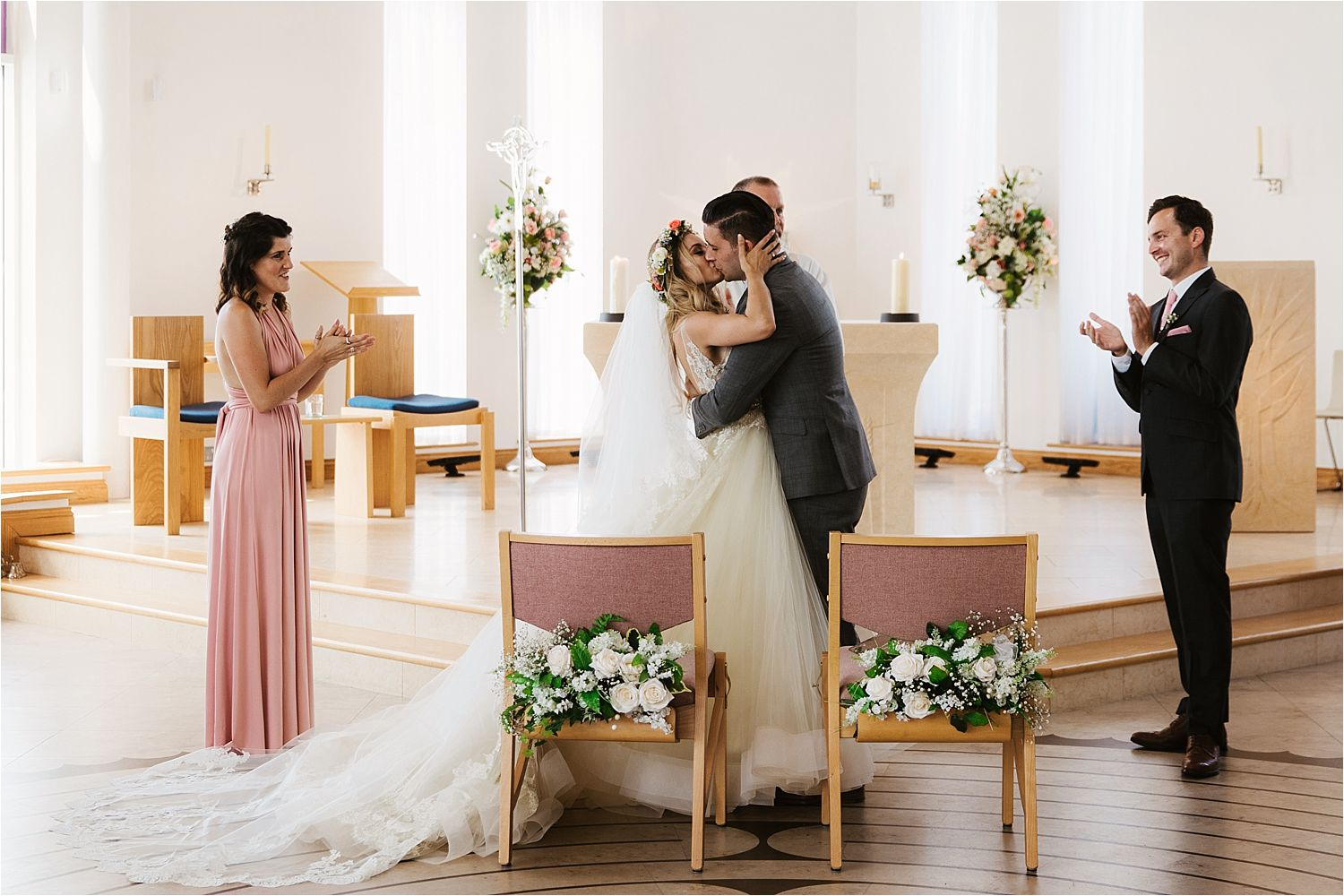 Bride and groom first kiss, wedding flowers by Green Earth Flowers, Cheshire. Dress by Lazarro