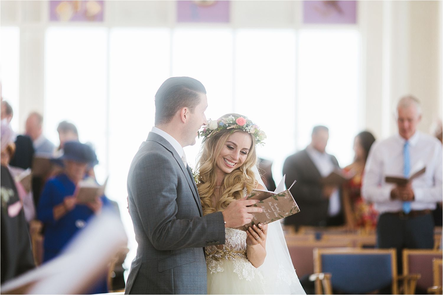 Bride and groom share a hymn book for their Cheshire wedding. Stationery by Rebecca Bright