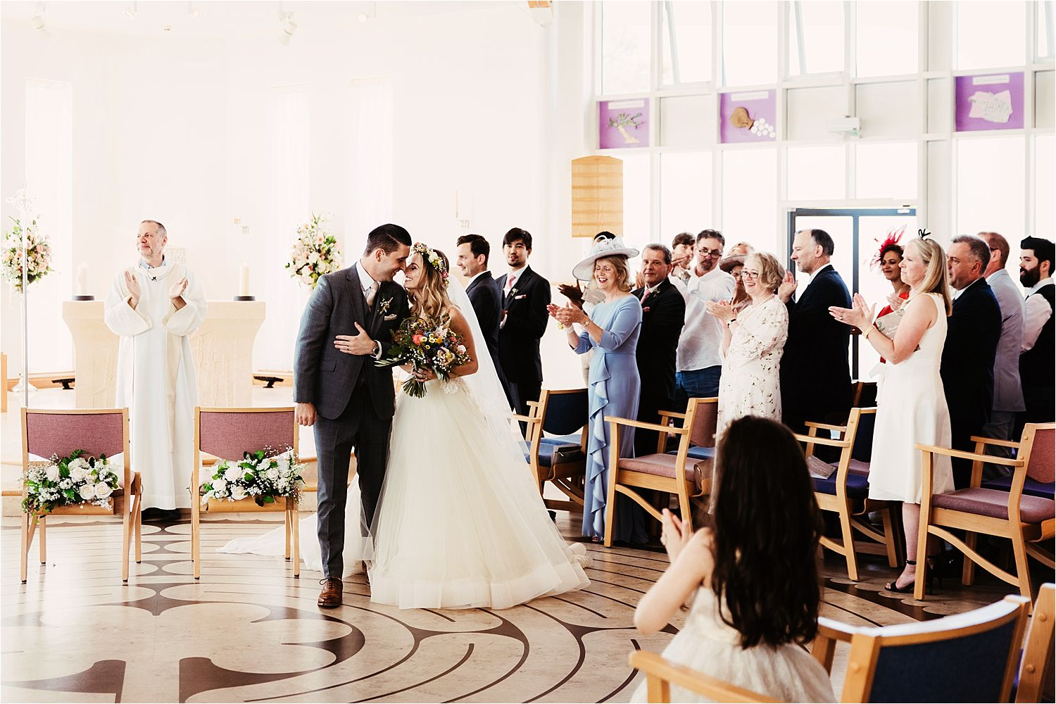 Congregation claps for the newly weds at their Cheshire wedding ceremony