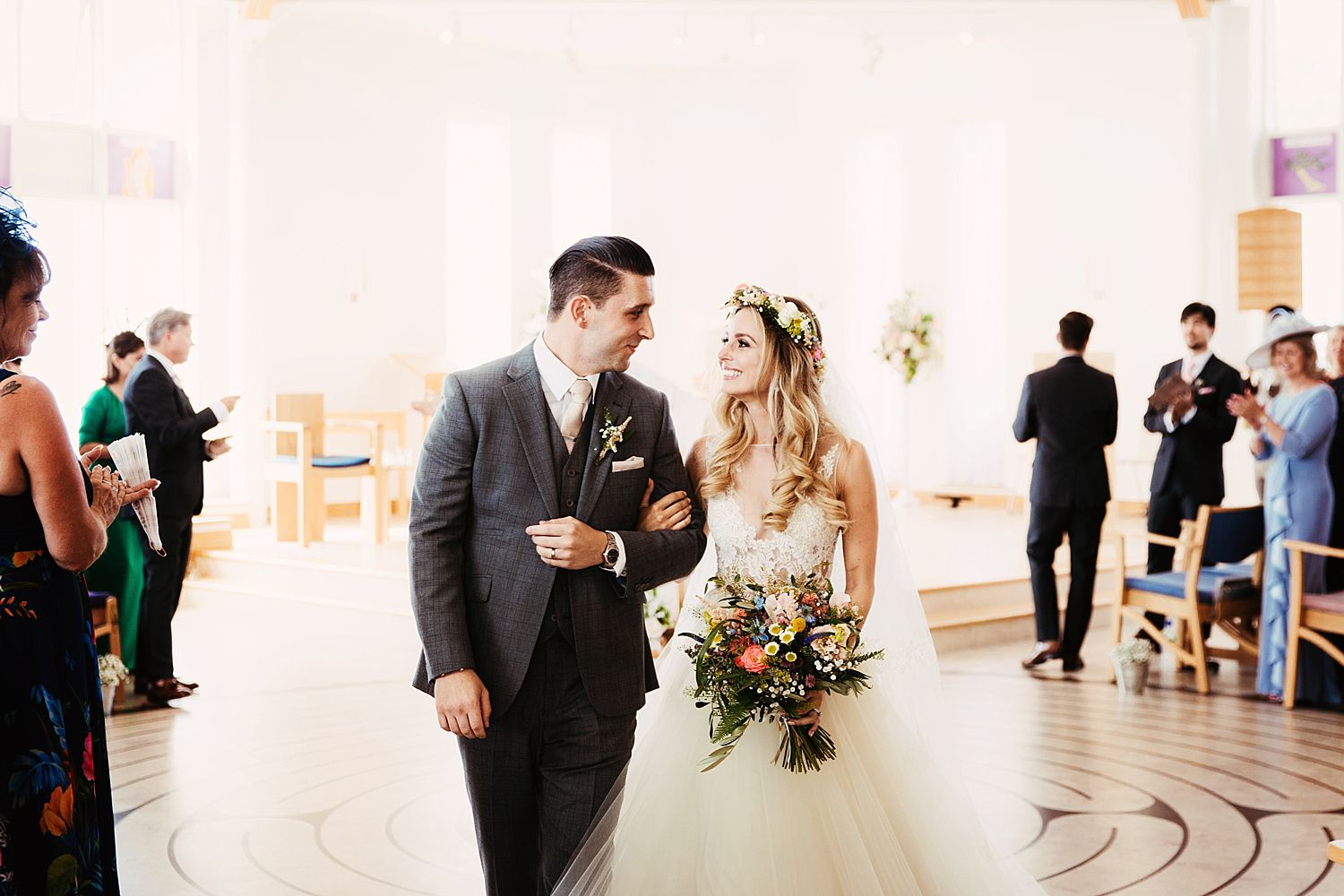 Bride and groom walk down the aisle after their Cheshire wedding, flowers by Green Earth Flowers