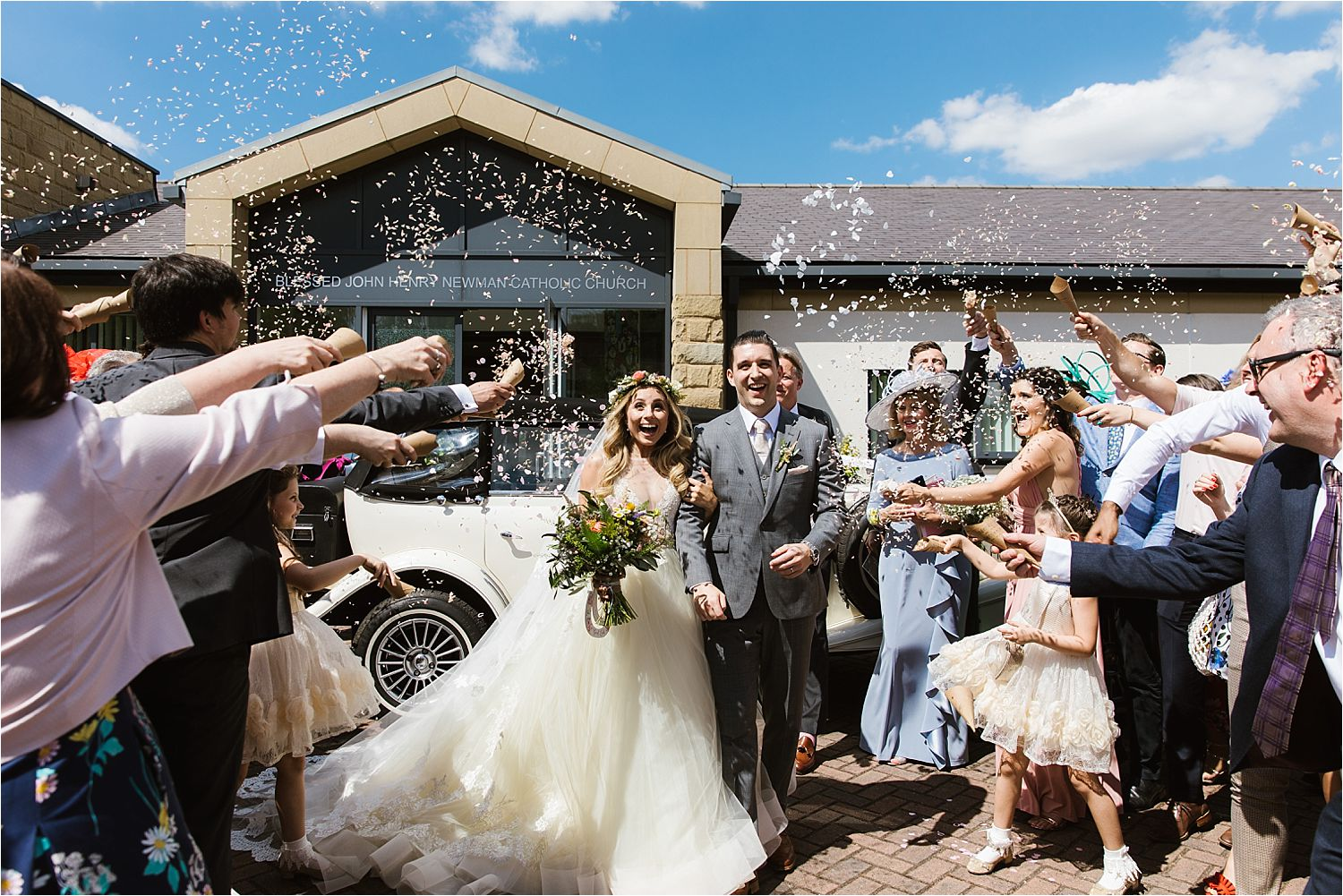 Bride and groom walk through confetti shower outside church at Cheshire wedding