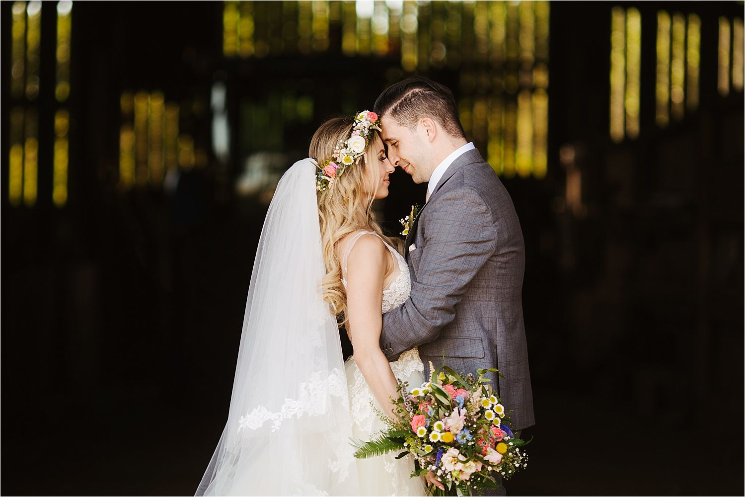 Bride and groom embrace, Flowers by Green Earth Flowers and wedding dress by Lazarro