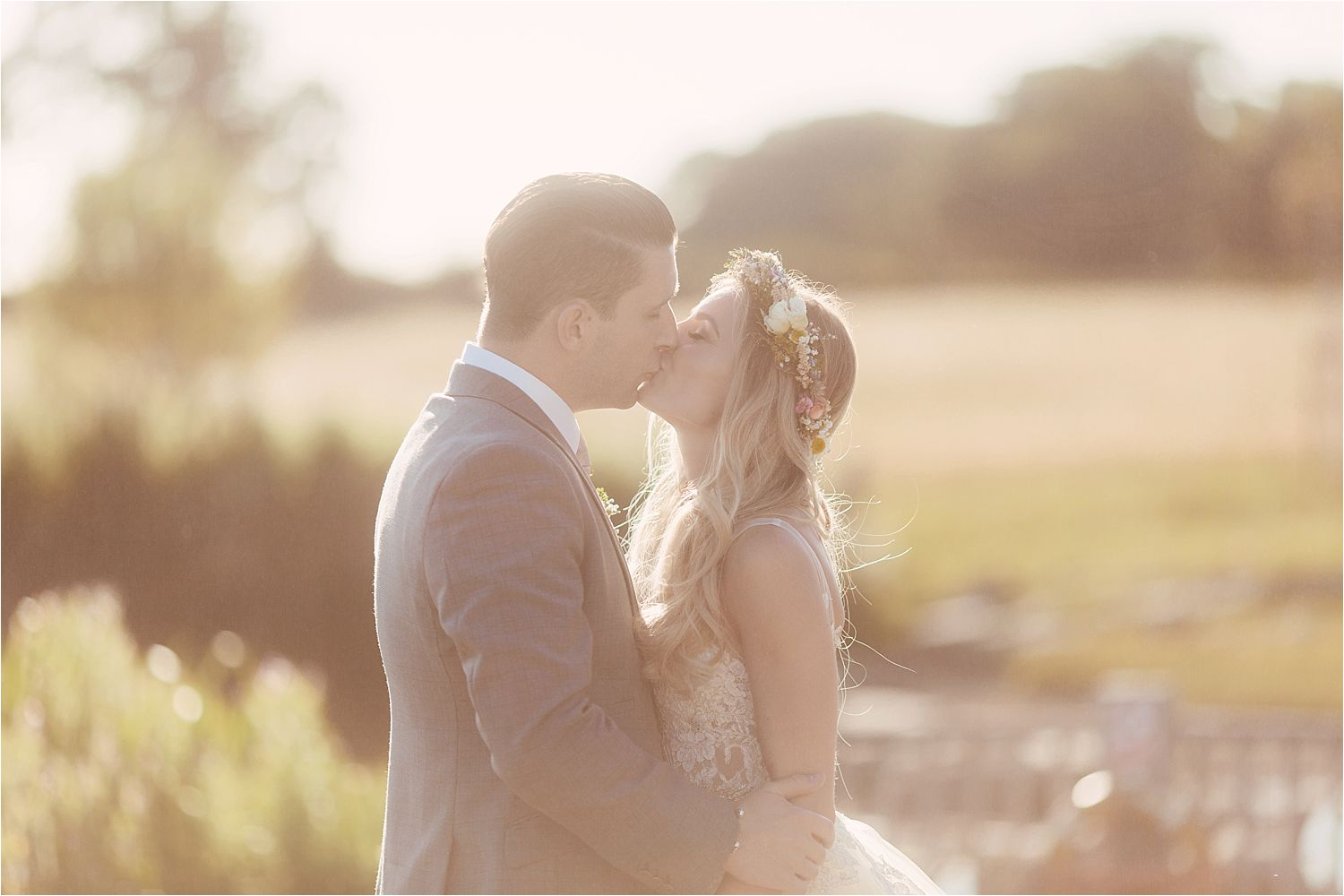 Bride and groom kissing in ground of wedding venue in Congleton Cheshire, Sandhole Oak Barn. Dress by Lazarro