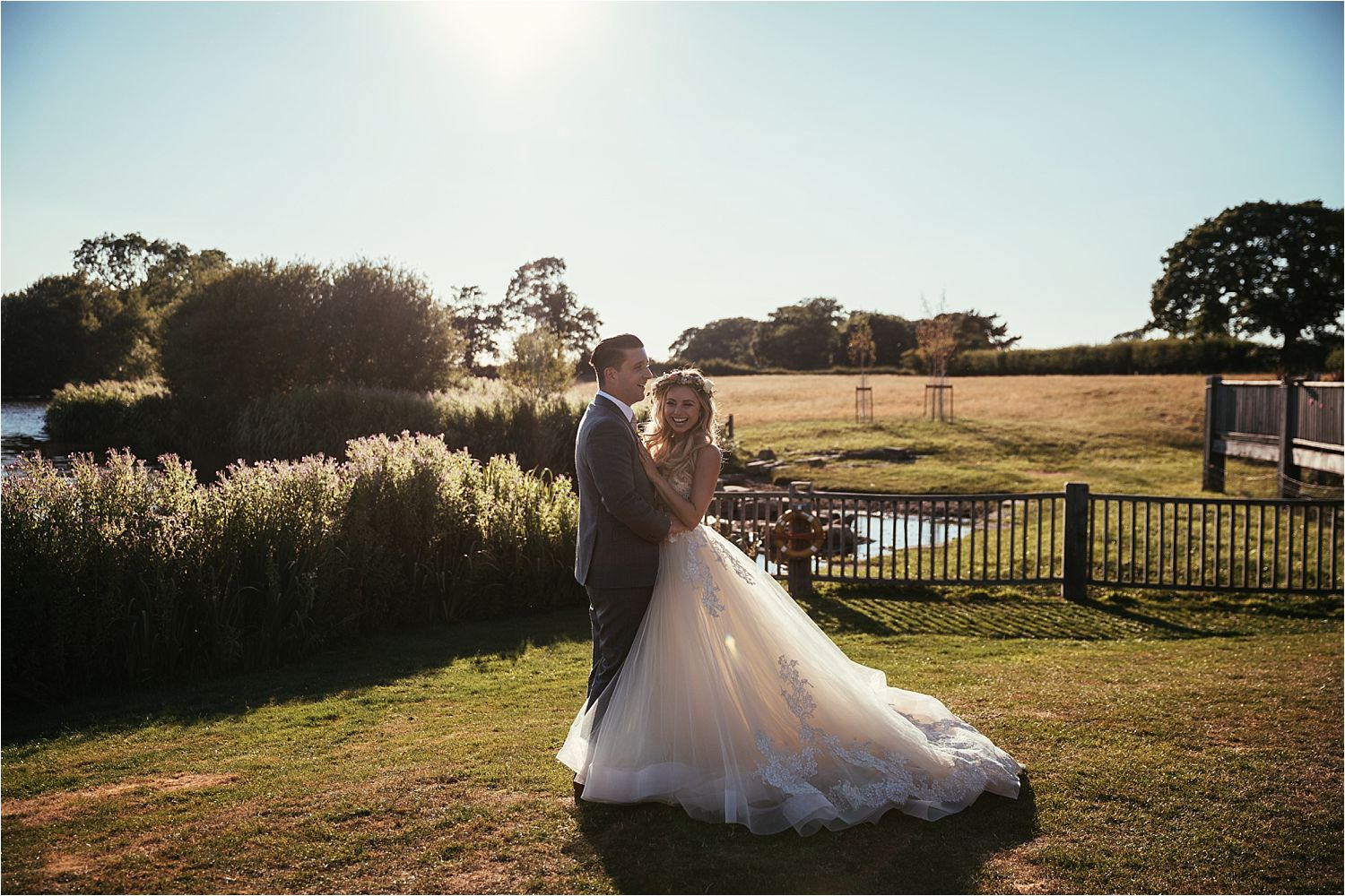 Bride and groom by side of lake at Sandhole oak Barn wedding venue, Cheshire. Dress by Lazarro