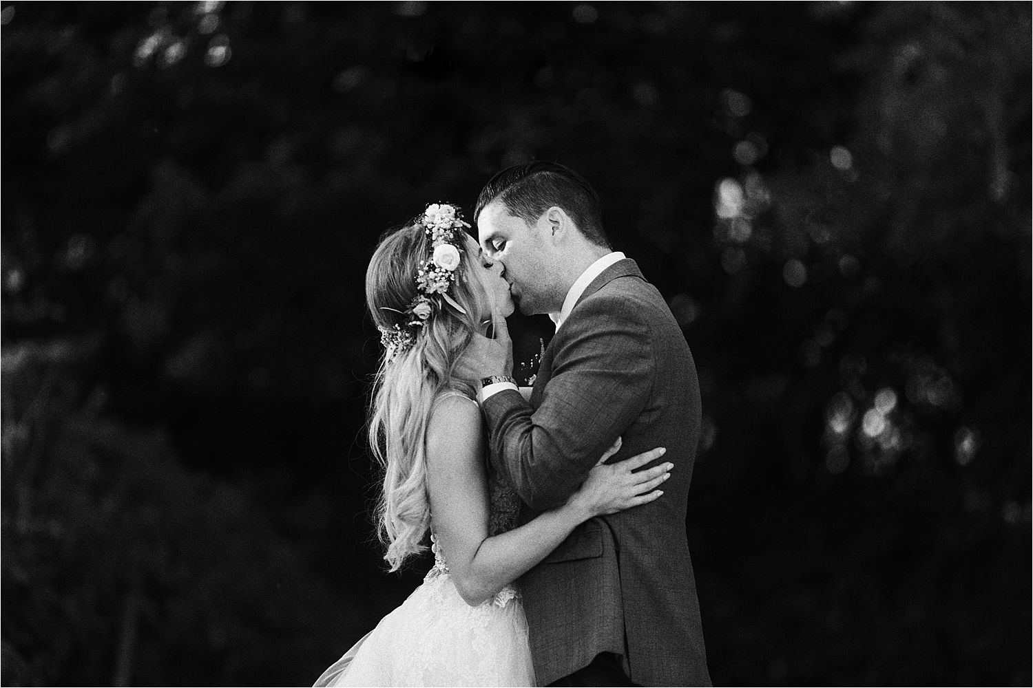 Black and white image of bride and groom kissing at Sandhole Oak Barn wedding Cheshire