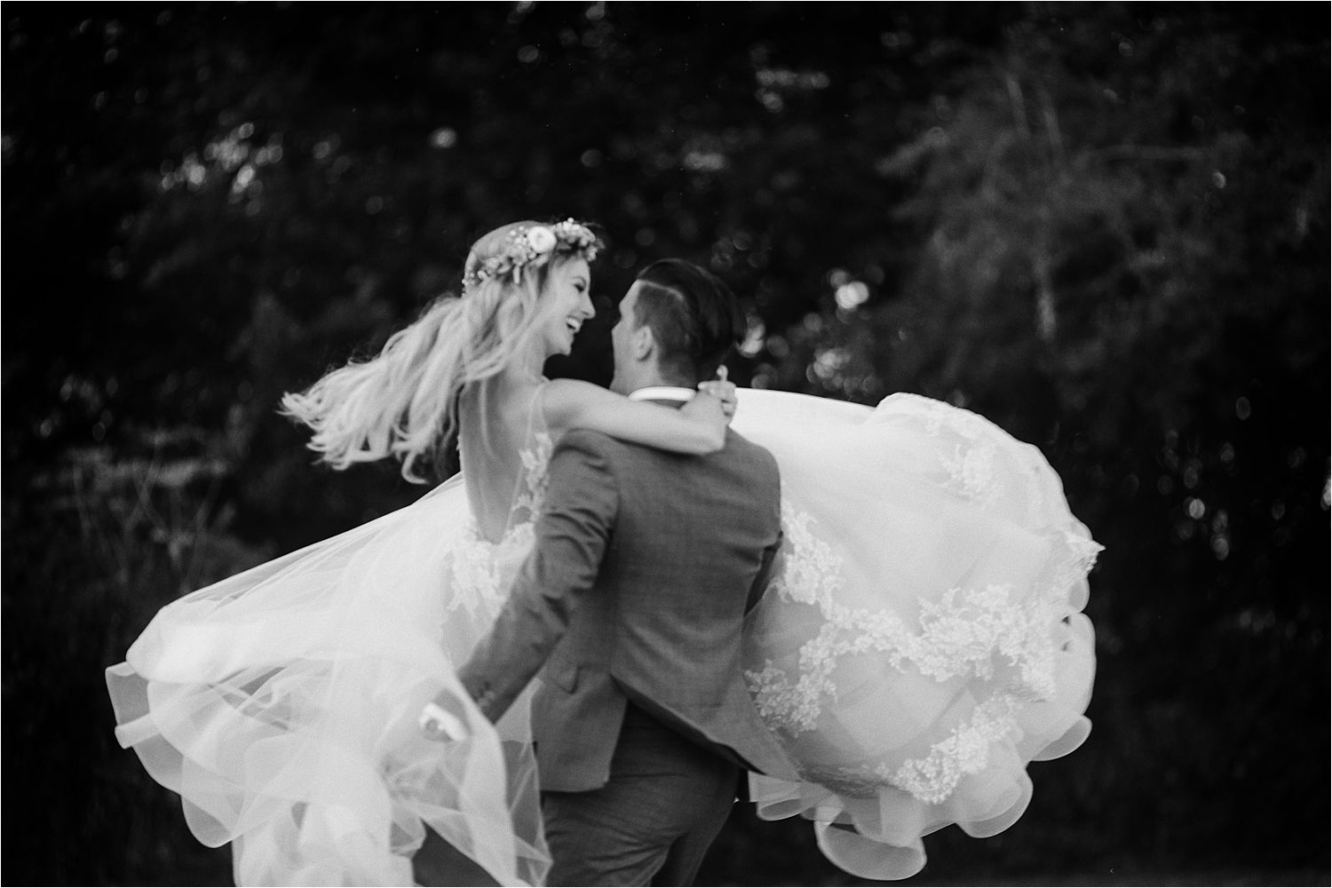 Groom swings bride round, wedding dress by Lazarro