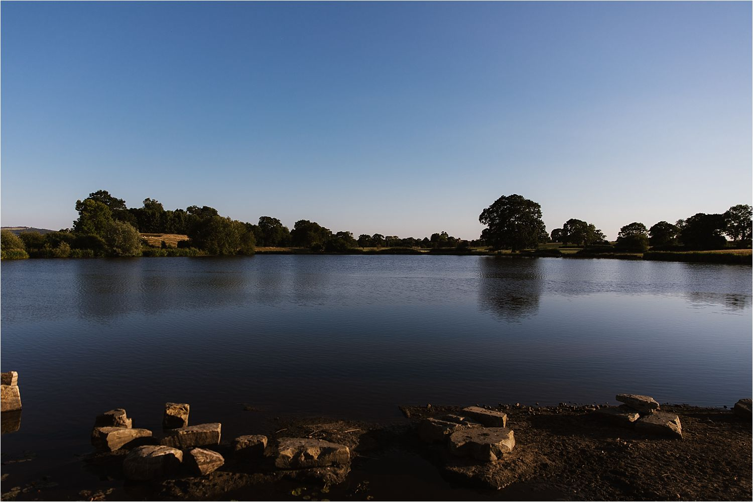 View of lake at sunset at Sandhole Oak Barn wedding venue in Cheshire