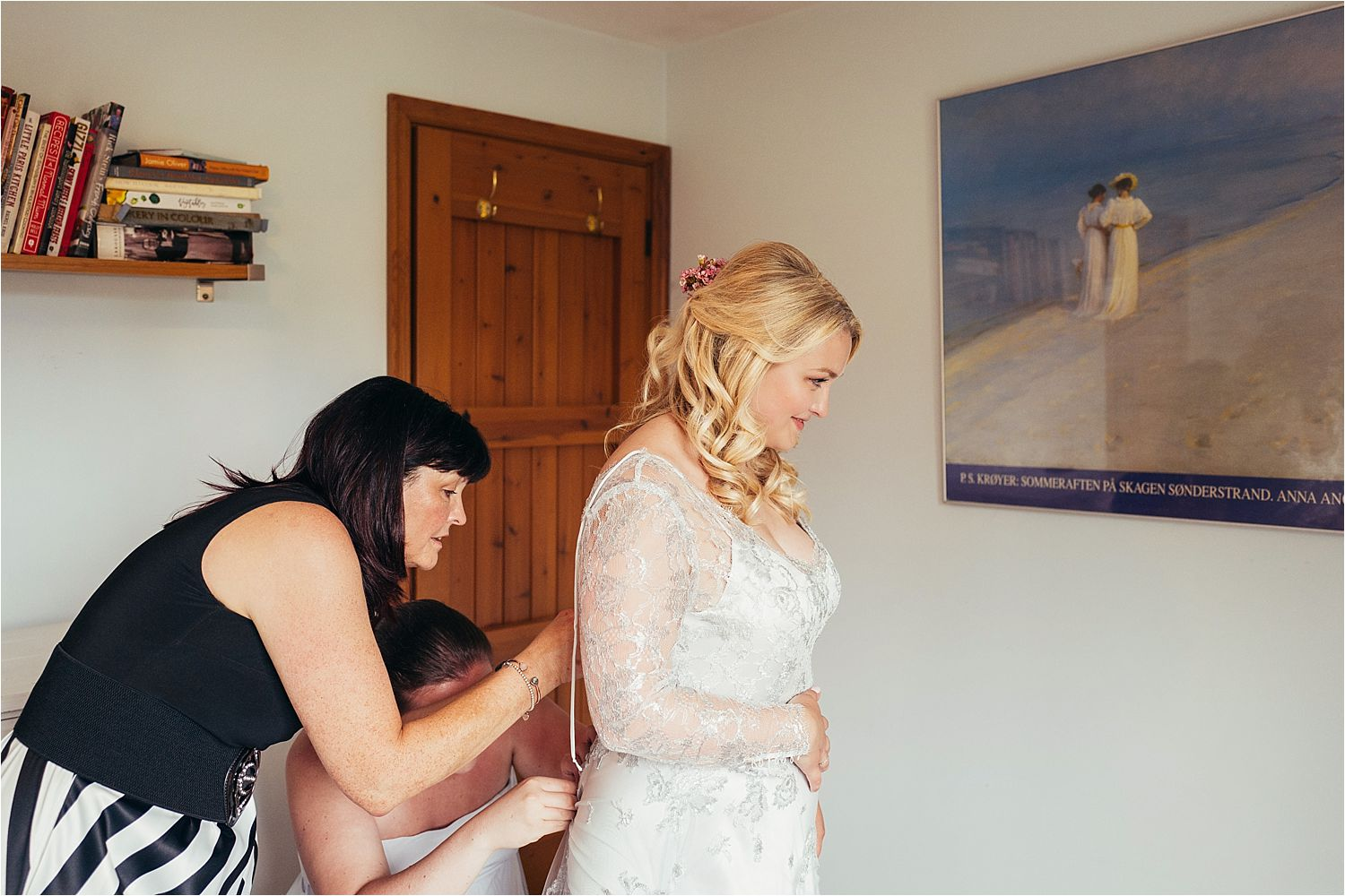 Bride being laced into her dress by Soon Bride