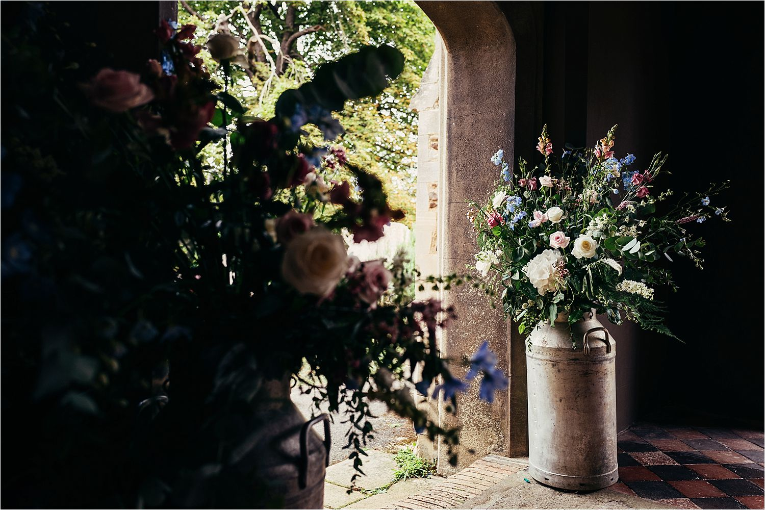Flowers in milk churns in the church doorway for Bedfordshire wedding