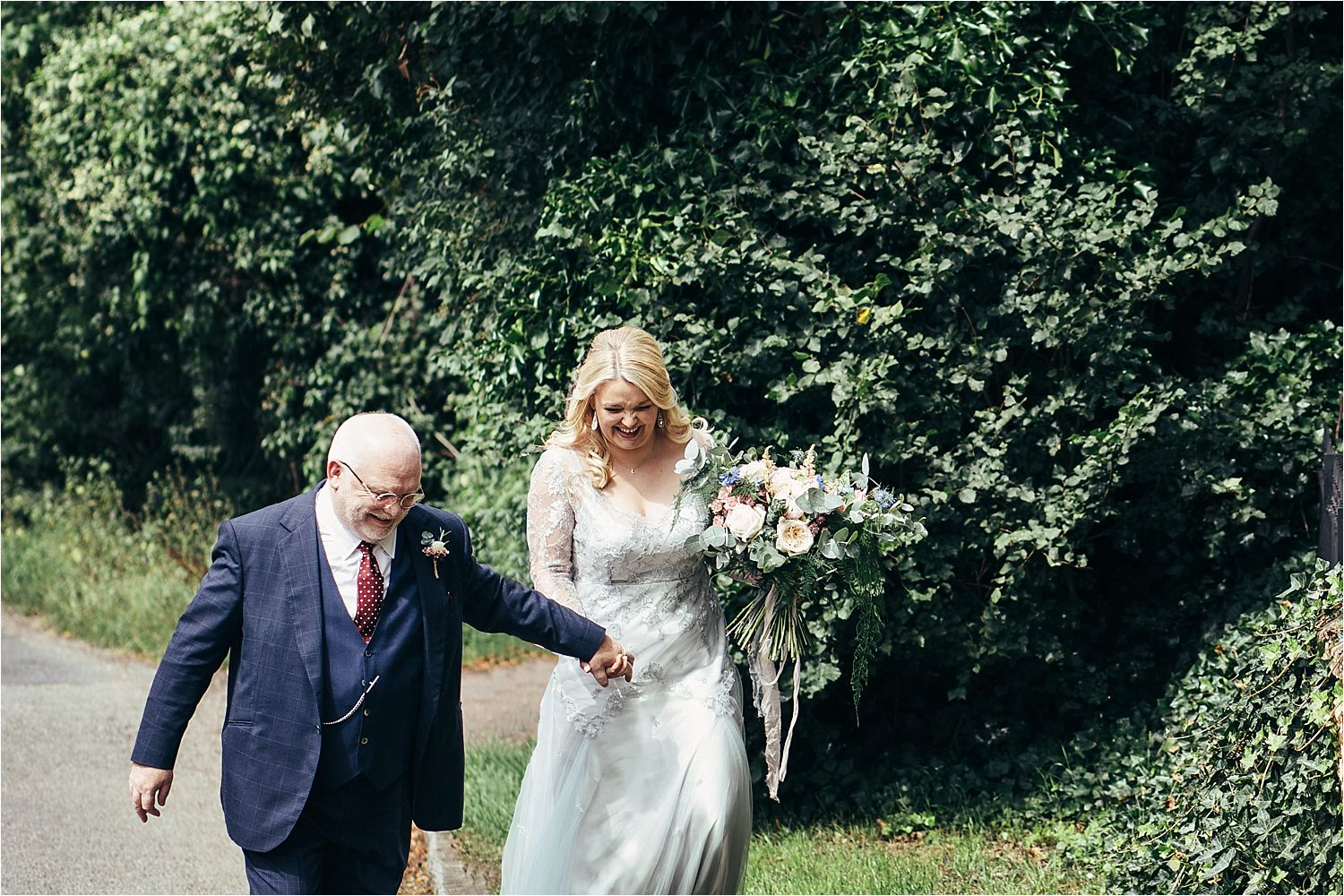 Bride and her father walk to church for Bedfordshire wedding. Bride's dress by Soon Bride