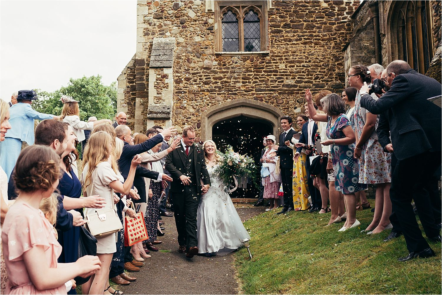 Bride and groom walking through confetti shower at Bedfordshire church wedding