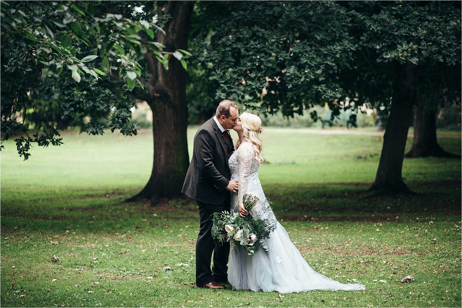 Bride and groom kissing at Bedfordshire wedding. Bride's dress by Soon Bride