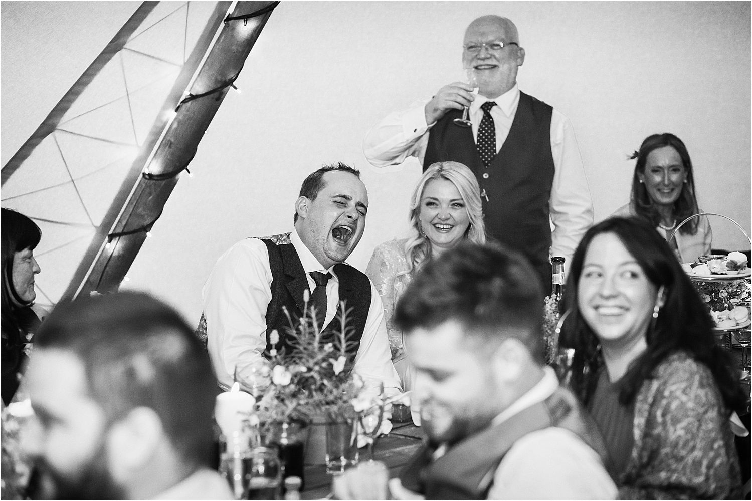 Raising a glass at tipi wedding reception