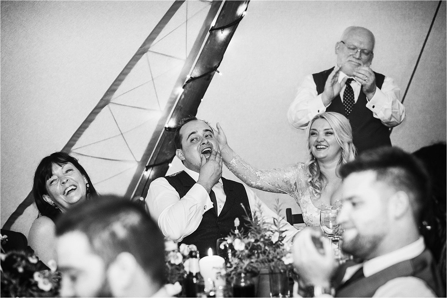 Bride and groom enjoying speeches at tipi wedding reception