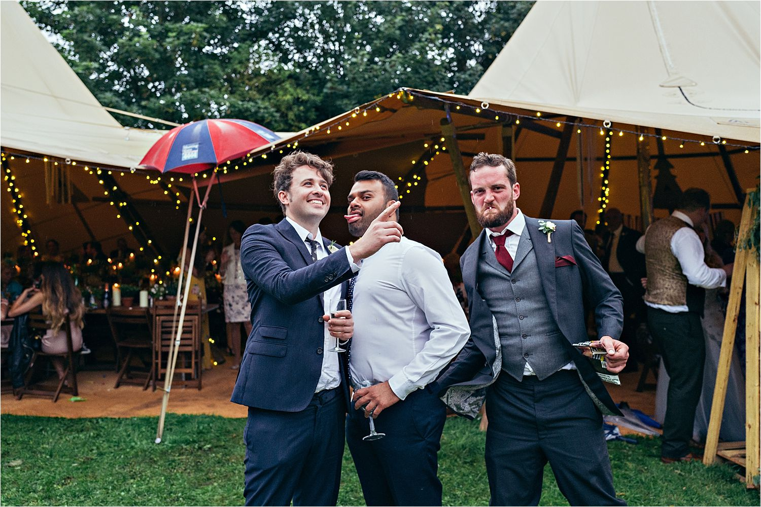 Men pulling faces outside tipi at Bedfordshire wedding reception. Tipi by Country tipis