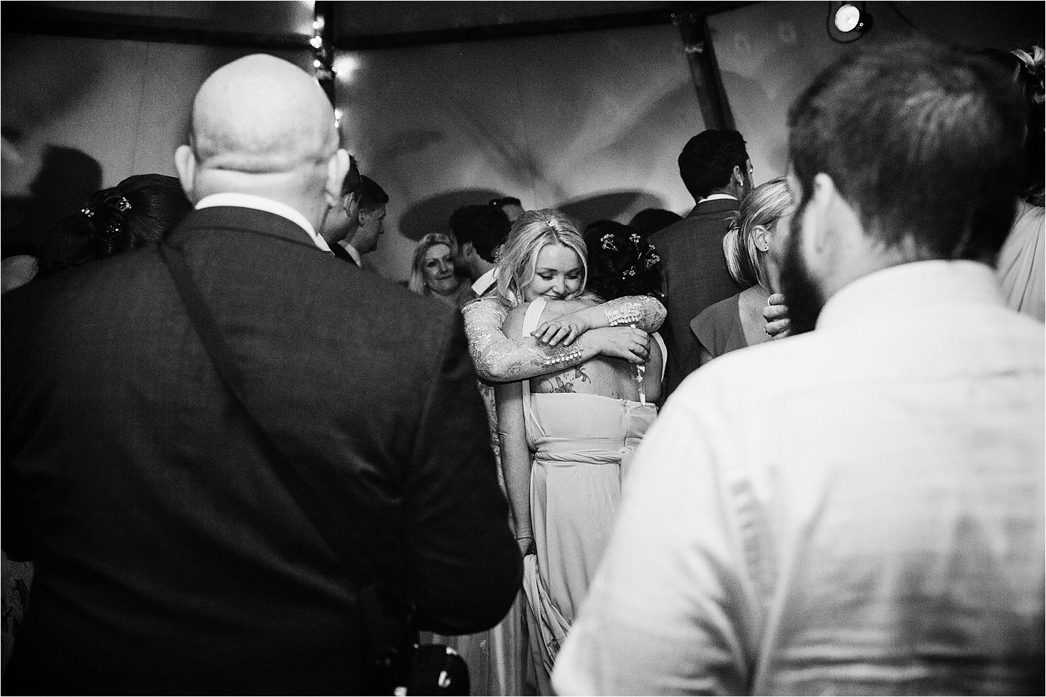 Bride embraces bridesmaid on dancefloor in Country Tipis wedding