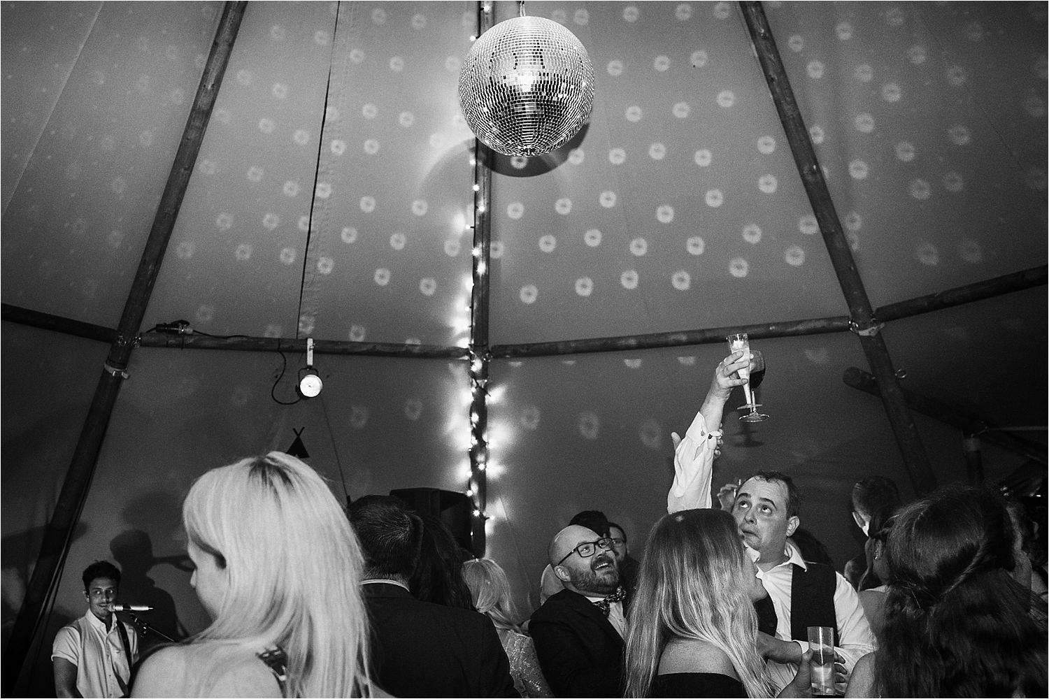 Glitterball and adncers at wedding evening reception in tipi