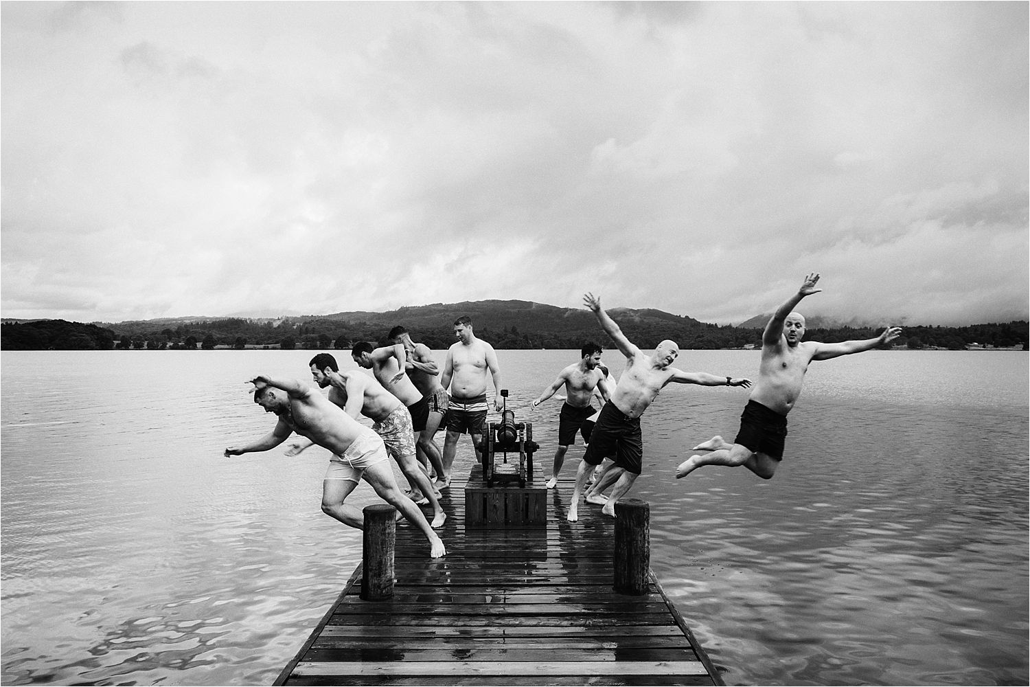Groom, best man and ushers diving into Lake Windermere prior to Low Wood Bay Hotel wedding