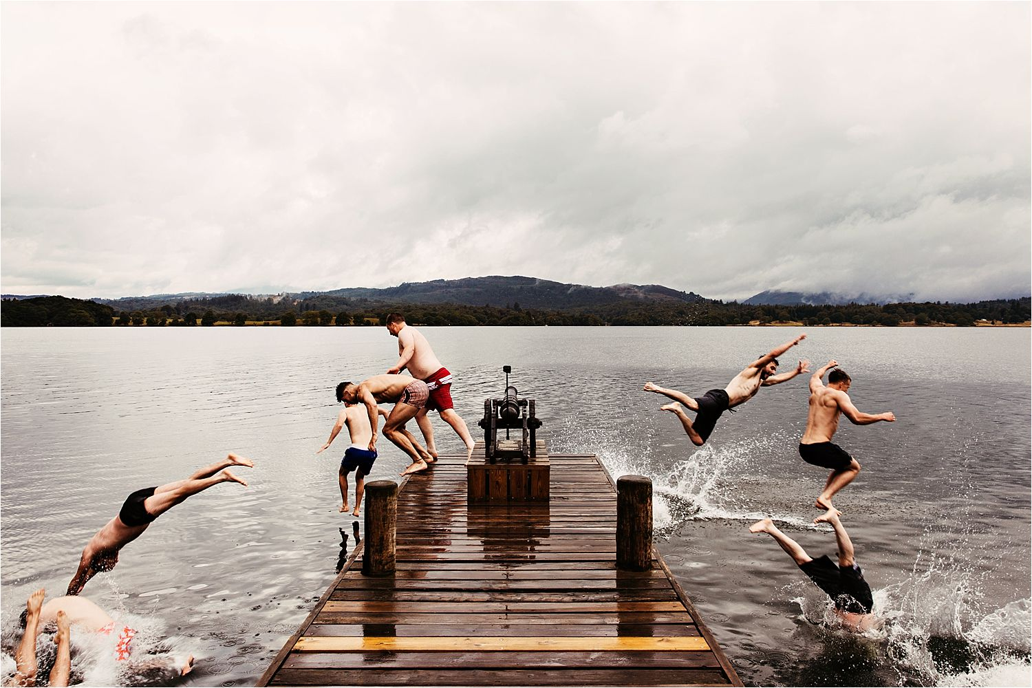 Grooms men diving into Windermere Lake before the wedding at Lake District wedding venue, Low Wood Bay Hotel