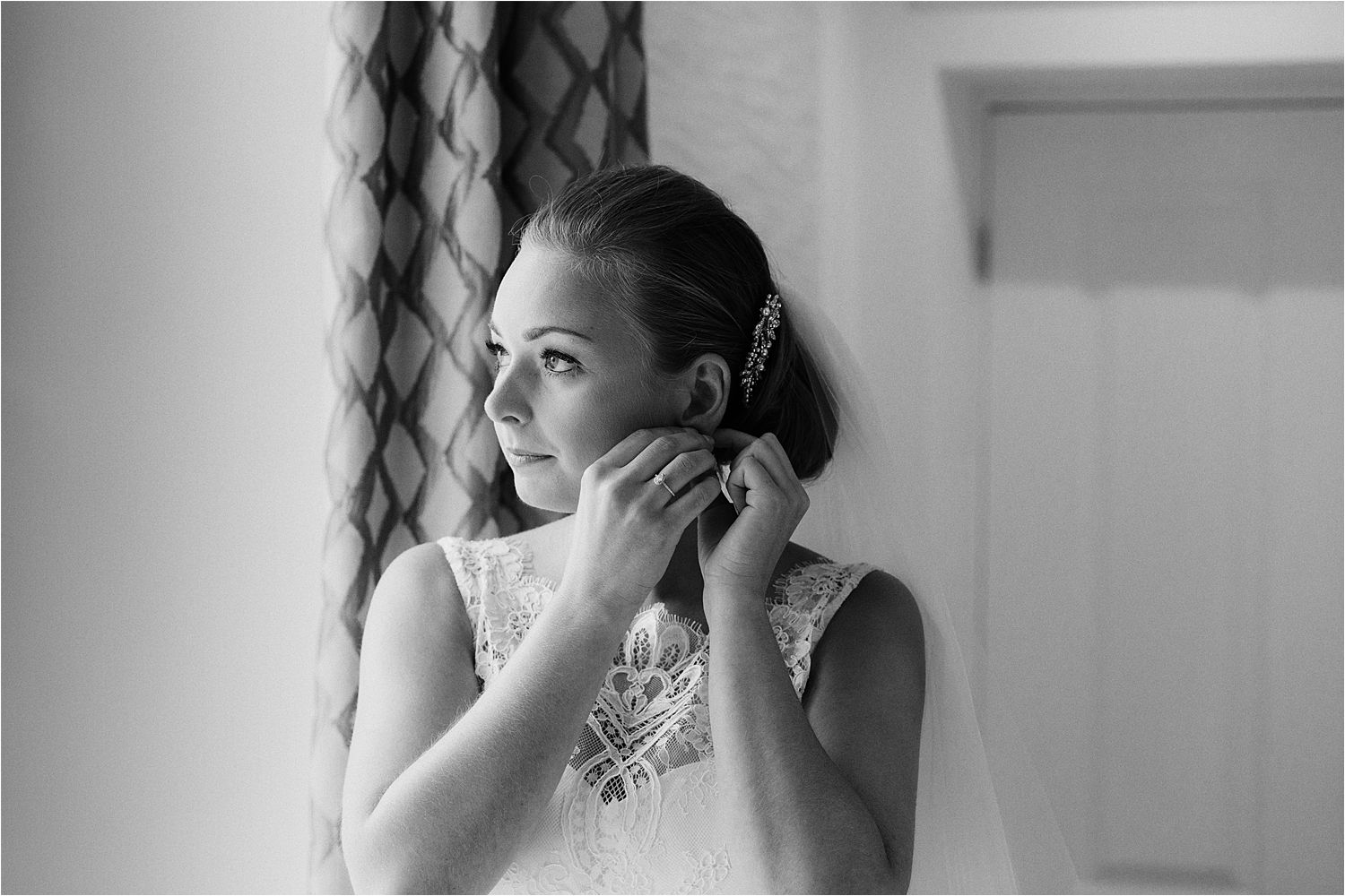 Bride puts on her earrings as she prepares for her Lake District wedding