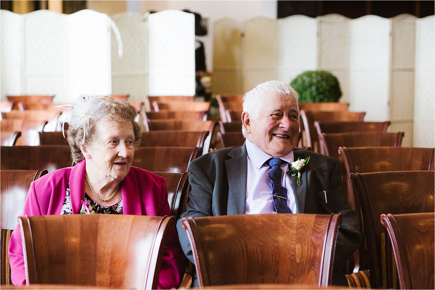A jolly older couple sitting waiting for the wedding to start at the Low Wood Bay hotel in Windermere