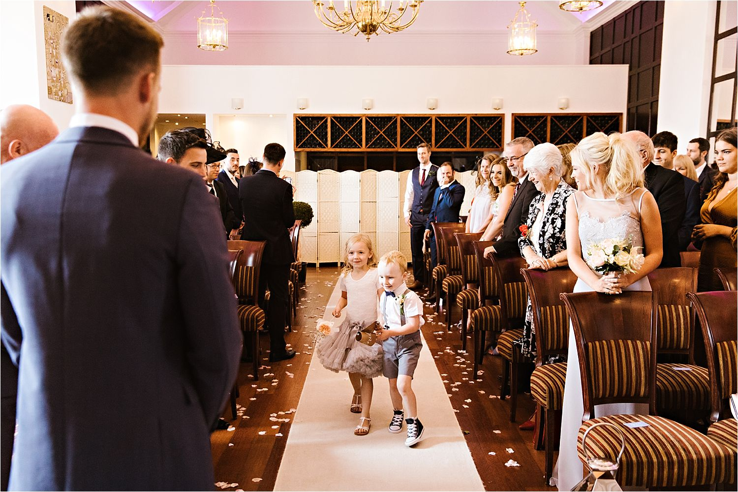 Flower girl and page boy walk down the aisle at Low Wood Bay wedding