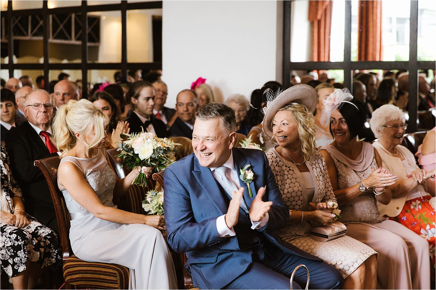 Bride's father claps during wedding ceremony at Low Wood Bay
