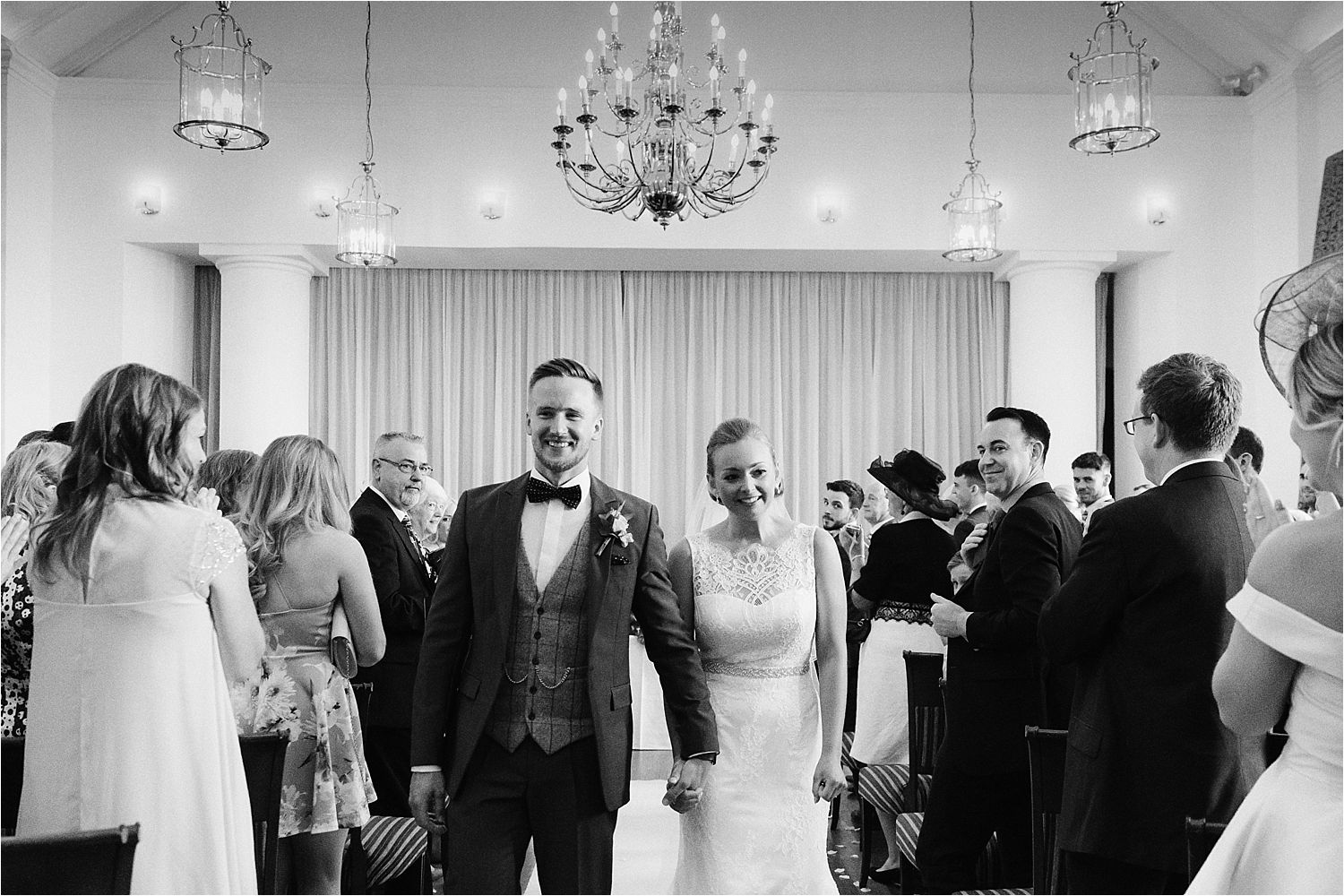 Wedding couple wlak down the aisle after their Low Wood Bay wedding ceremony. Grooms suit by Whitfield and Ward