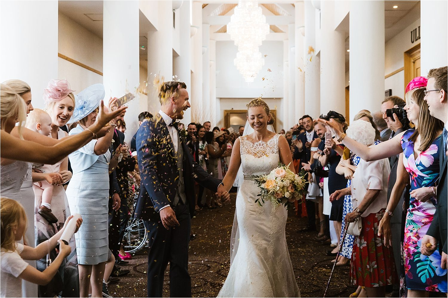 Confetti shower for bride and groom. Bride's dress Augusta Jones at Mears Ghyll