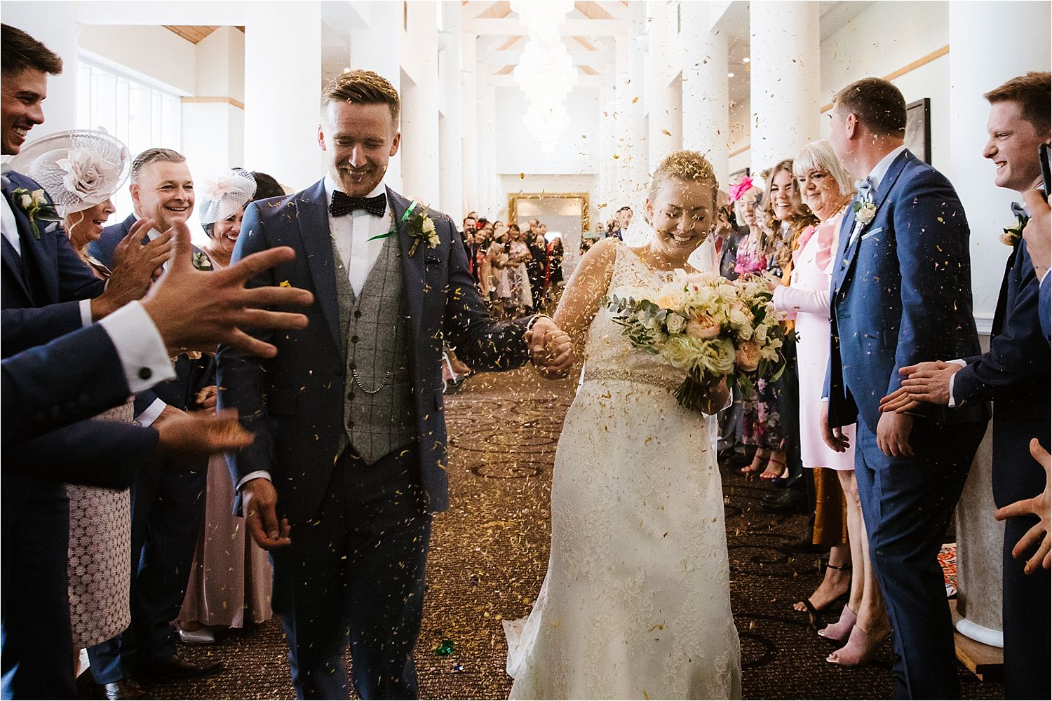 Bride, groom and confetti at their Low Wood Bat wedding. Groom's suit by Whitfield and Ward