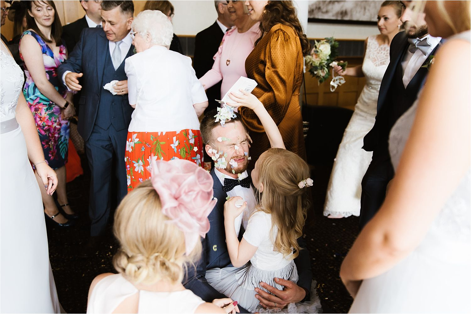 Flower girl empties confetti on groom's head at Low Wood Bay wedding