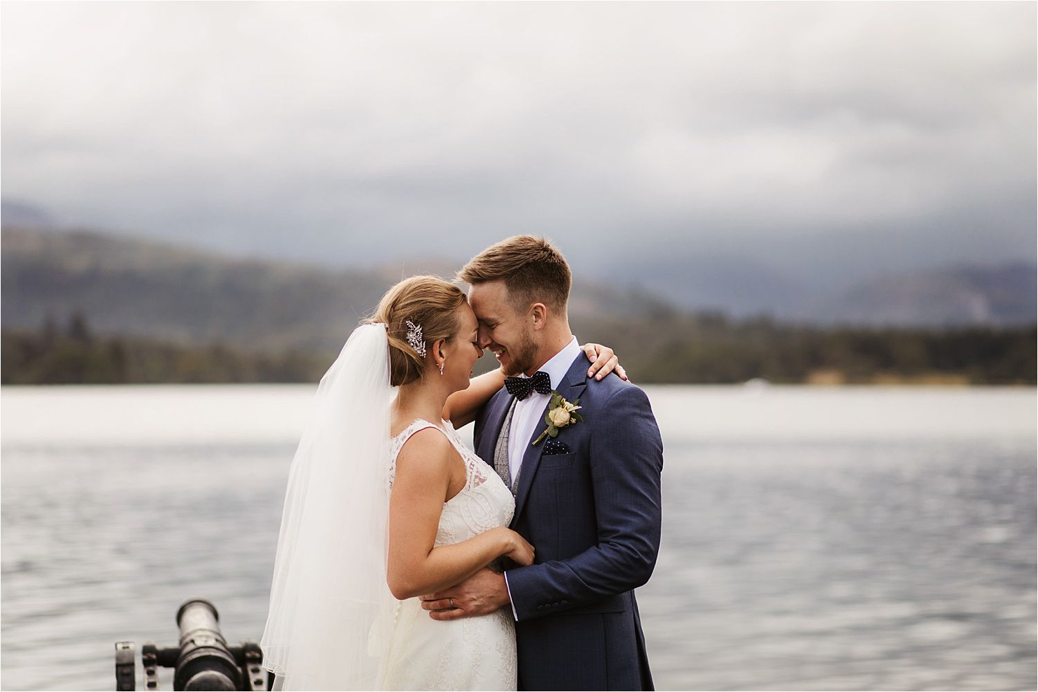 Bride and groom, heads together on jetty with Lake Windermere in background