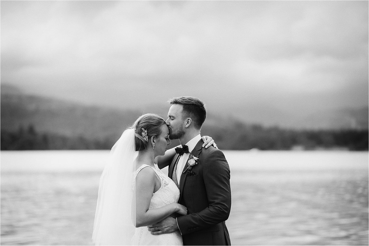 Bridegroom kisses ride's forehead on jetty at Lake Disrtict wedding.