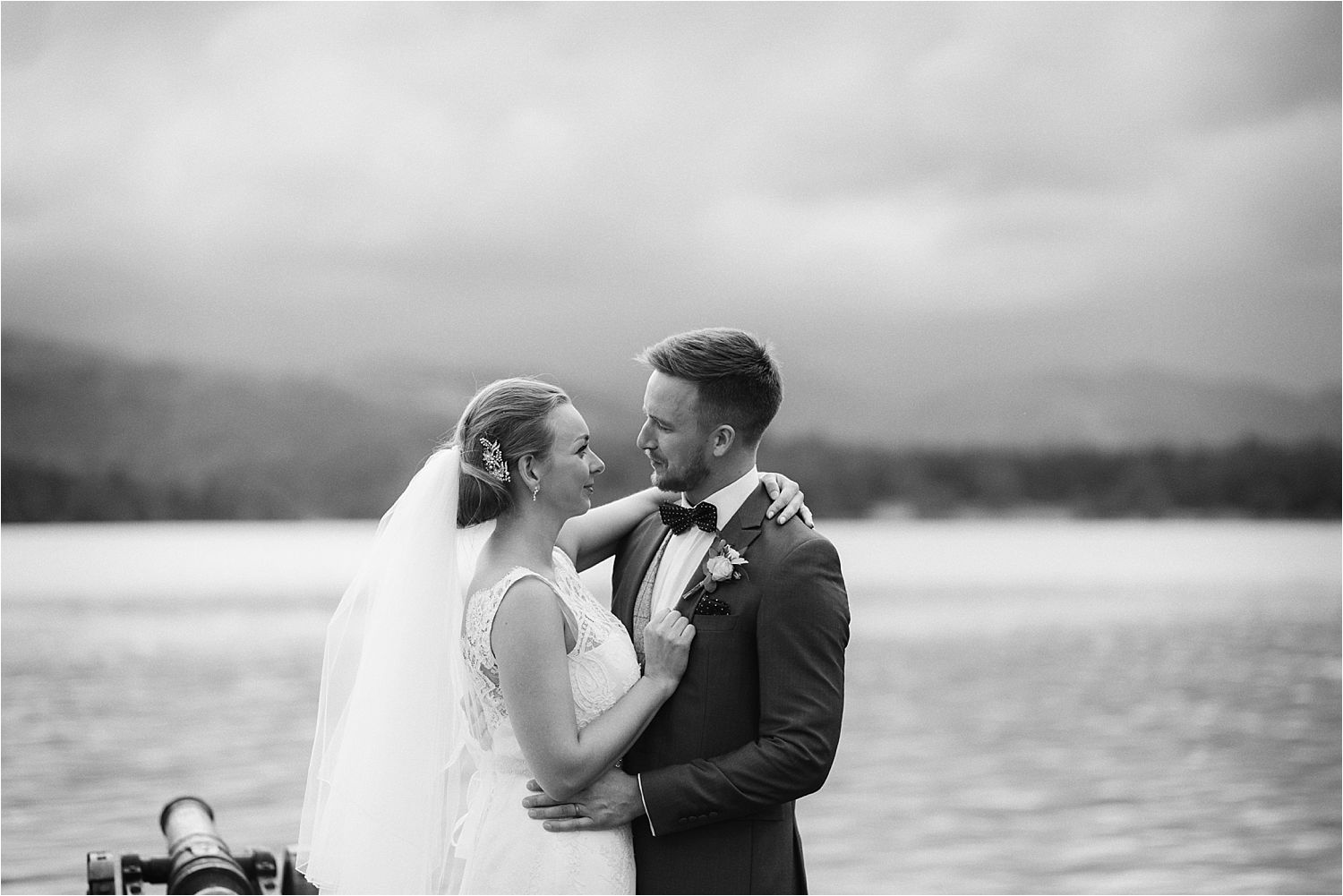 Bride and groom on Low Wood Bay jetty with Lake Windermere in background
